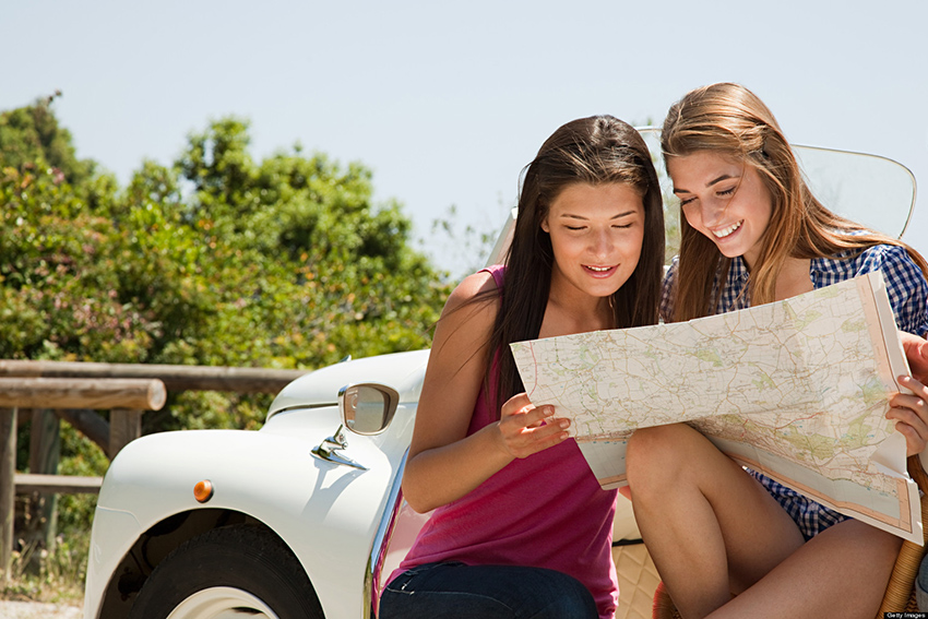 Young women with convertible car looking at map