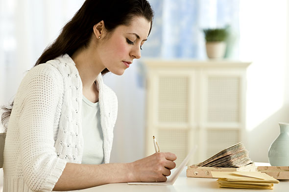 woman-writing-on-table-590kb101310